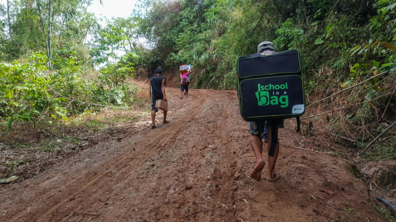 Smart employees and locals of Maasin, Iloilo hike up a muddy trail for 1.5 hours to deliver digital learning tools to Trangka Elementary School.